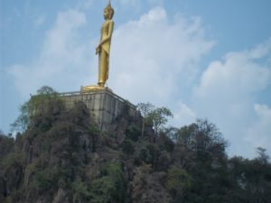 Trains pass a hilltop Golden Buddha