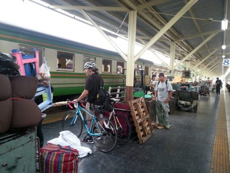 Man waiting to place his bicycles in the cargo car at Bangkok train station